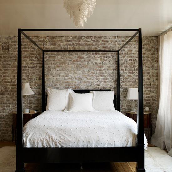 Maskulint sovrum med mörkt trä och rå tegelvägg