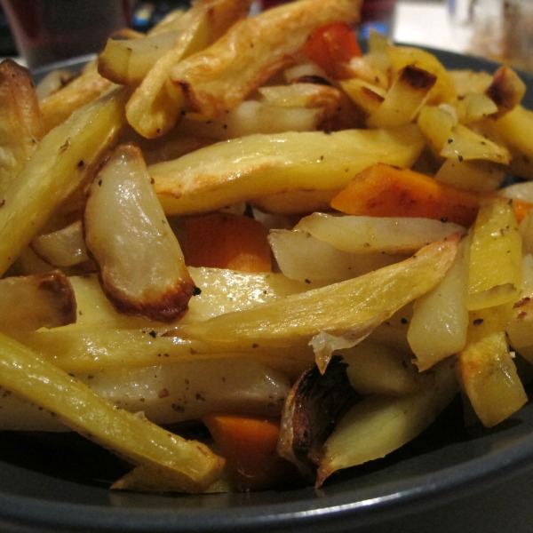 Mandelpotatis, potatis, morot och gul lök rostade i olja och kryddade med svartpeppar och salt